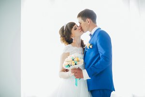 Bride and groom in studio light stand  kiss on a white background