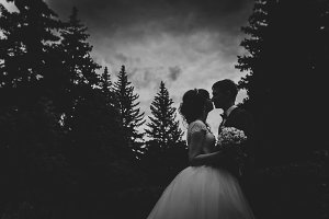 black and white photo of bride  groom silhouettes kissing on nature background