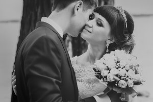 black and white photo of bride  groom kissing on the background  trees