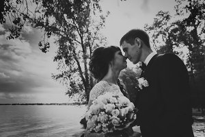 black and white photo of bride  groom standing  kissing in the background  the nature