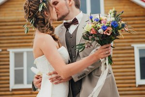 Bride and groom kissing hugging on the background of the house