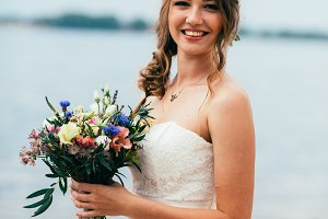 young bride with a bouquet of flowers standing on the background  the river