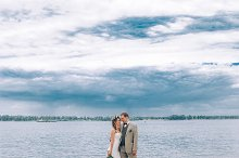 young groom and bride standing hugging on the background of the river