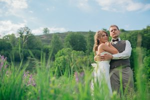 the bride and groom with a bouquet in the grass against the background mountain landscape