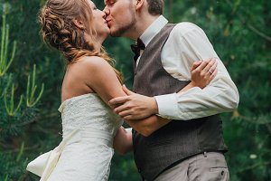 bride and groom kissing on the background of forest