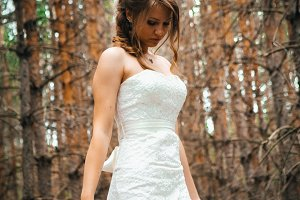 Bride with a tattoo on  background of leaves and forest backlight