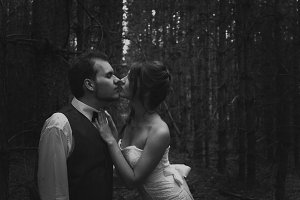 black and white photo of bride  groom on the background  leaves  wood backlight