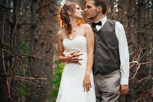 dramatic picture bride and groom on the background of leaves forest backlight