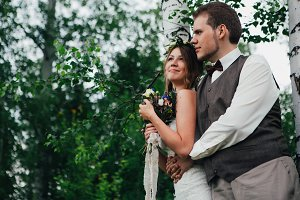 portrait of a bride and groom embrace on background leaves forest