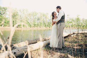 bride and groom standing arm in  against the background grass  lakes