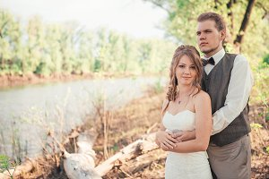 bride and groom standing on a background of grass  lakes