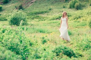 bride stands on a background of grass and mountains