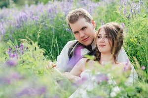 portrait of the bride and groom resting on a lavender background