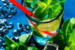 glass of mojito with lime and mint ice cube close-up red straw on blue background