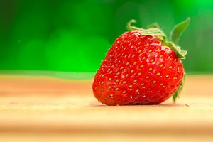 One berry fresh strawberries on a blurred background