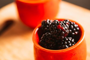 Blackberries in a cup on blurred background of wooden planks