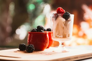 Blackberry ice cream in a cup and  glass on  background of wooden boards   blurred green