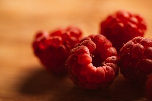 Raspberry on a blurred background of wooden planks