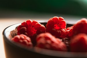 raspberry in a cup on  blurred background of wooden planks