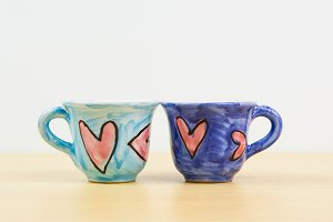 Colorful coffee cups with hand draw of love heart on wood board