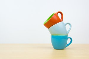 Colorful stack coffee cups on wood board