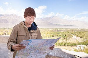 Young Asian tourist lost in mountain peak and looking at the map during summer