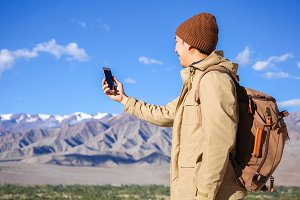 Young Asian hiker using a smartphone on top of mountain peak