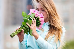 woman smelling pink rose flowers