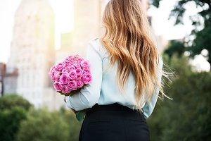 girl holding bouquet of pink roses