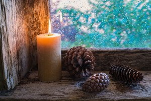 lit candle and pine cones