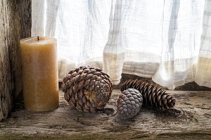three pinecones and a candle