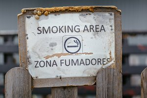 Aged smoking area sign with snails