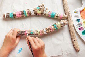 Hands of a child painting driftwood