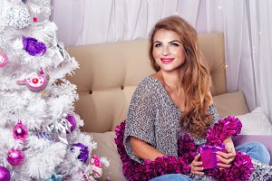 Girl sits on sofa. Christmas tree