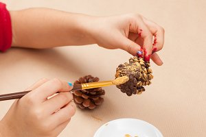 Children painting pine cones