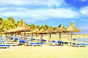 Straw umbrellas on beach Tenerife