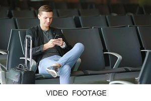 Young man with cellphone at airport