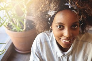Close up shot of beautiful African girl with healthy freckled skin and do-rag on her head, dressed casually, sitting on windowseal at home, looking and smiling at camera with flowers on background