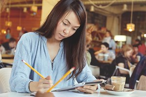 Headshot of young attractive student girl with long dark hair sitting at cafeteria with touch pad pc, doing her home assignment, writing down in her notebook using pencil before classes at university
