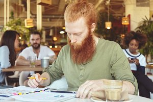 Portrait of young redhead freelancer with long beard holding pencil, hand drawing schemes and graphics, analyzing data using digital tablet while working on new project, sitting at coffee shop