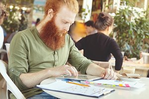 Handsome bearded student wearing casual clothes browsing Internet on his touch pad while doing home task on economics, sitting at coffee shop. Redhead freelancer messaging online via social networks