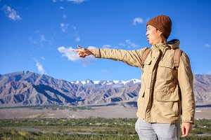 Young Asian traveler pointing out his finger for next destinations in high hill and blue sky background in Leh, Ladakh, India