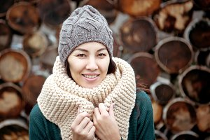 Beautiful smiling brunette woman wearing knitted scarf and hat.