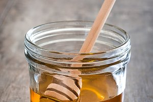 Honey dipper with honey in a jar