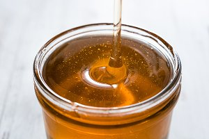 Pouring honey in a jar