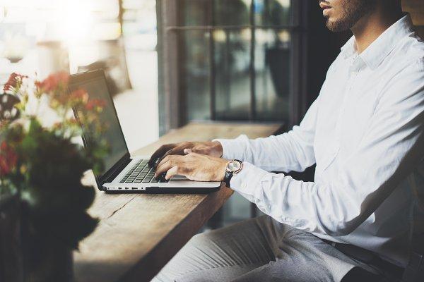 Businessman using laptop at cafe