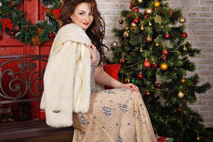 Girl in fur coat near Christmas tree