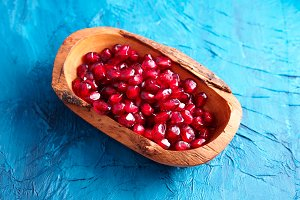 Pomegranate seeds on blue