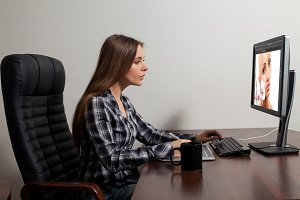 woman sits in front of computer