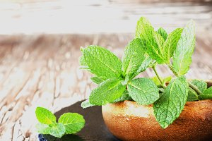 Fresh mint in a wooden bowl, selective focus